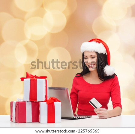 christmas, shopping and people concept - smiling woman in santa helper hat with gift boxes, laptop computer and credit card over beige lights background - stock photo