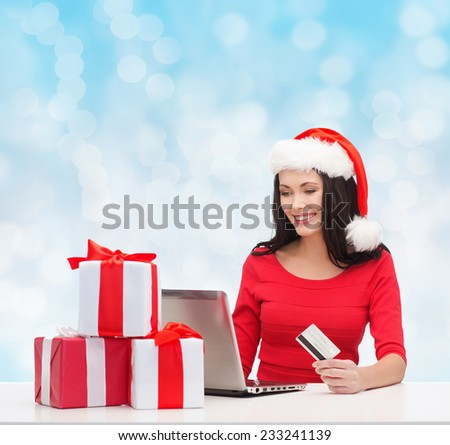 christmas, shopping and people concept - smiling woman in santa helper hat with gift boxes, laptop computer and credit card over blue lights background - stock photo