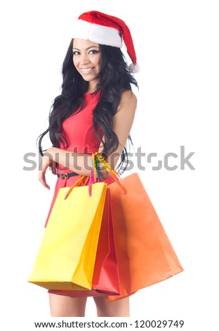 Christmas Shopping, Asian woman holding colorful shopping bags wearing santa hat on white background - stock photo