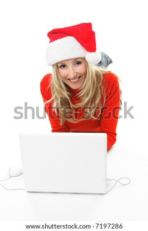 Christmas Shopping online.  A girl using a laptop computer is browsing the internet and shopping online for gifts.  She is looking up from teh computer and smiling - stock photo