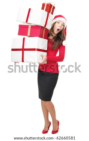 Christmas shopping. Santa woman standing holding many gifts with funny expression isolated on white background. Young mixed race Asian Chinese / white Caucasian model. - stock photo