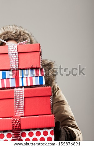 Christmas shopping stress - a woman in a winter anorak is hidden behind a tall stack of colorful decorative Christmas presents as she returns from a day out purchasing gifts - stock photo