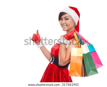 Christmas shopping woman thinking wearing santa hat and holding shopping bag. Female looking  smiling happy isolated on white background. - stock photo