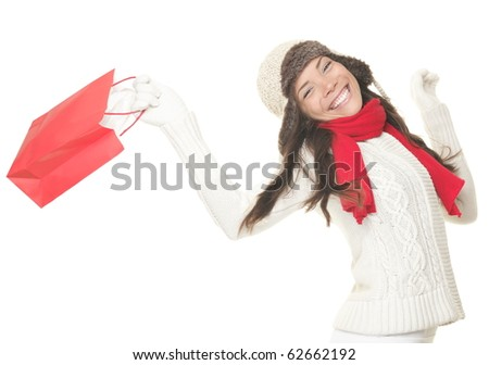 Christmas shopping woman with gift bag running joyful. Smiling young woman in winter clothes holding red shopping bags. Isolated on white background.