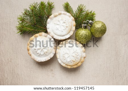 Christmas short crust pastry mince pies dusted with icing sugar on golden background next to Christmas ornaments and a twig of pine tree. - stock photo
