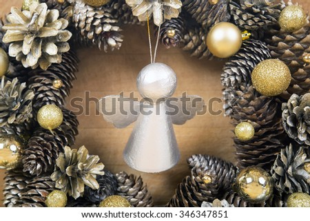 Christmas silver angel with wreath of cones and gold balls on background. - stock photo