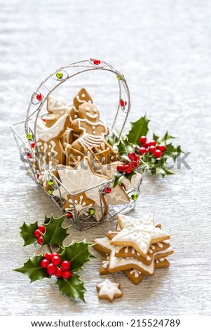 Christmas Silver background with holly branch, berries and gingerbread cookies. - stock photo