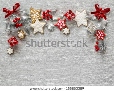Christmas Silver background with holly branch, berry and ginger cookies. - stock photo