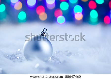 Christmas silver bauble in colorful blurred lights background - stock photo