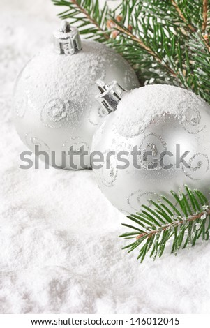 Christmas silver baubles and fir branches under snow. - stock photo