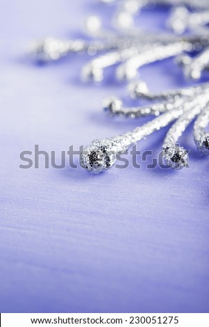 Christmas silver snowflake on light purple wood background with space for text. Merry christmas card. Winter holidays. Xmas theme. - stock photo