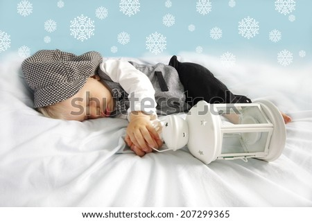 Christmas sleeping newborn baby with lantern in suit and hat on blue background with snowflakes. Photo for calendar, card  etc. Christmas concept. - stock photo