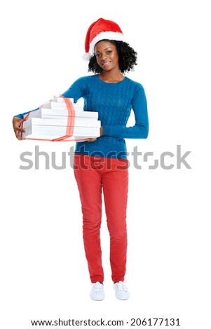 Christmas: Smiling african female with santa hat and holding a stack of gifts in studio - stock photo
