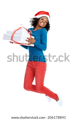 Christmas: Smiling african female with santa hat and holding a stack of gifts in studio and jumping - stock photo