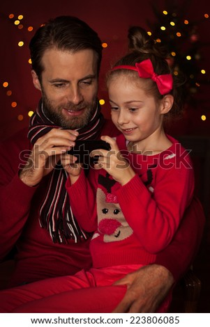 Christmas - smiling father and daughter playing game on mobile phone. Happy family time, dark red with lights as background. - stock photo