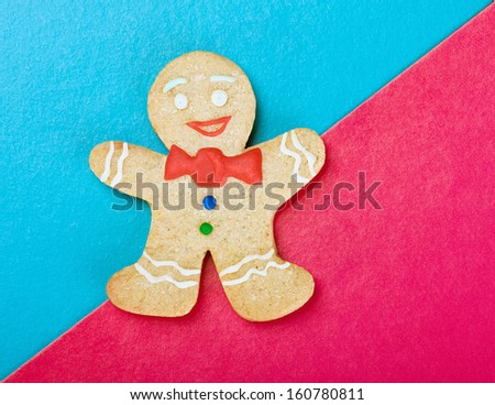 Christmas smiling gingerbread man on a colored background - stock photo