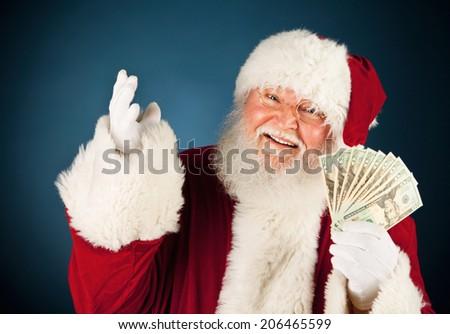 Christmas: Smiling Santa Holding Up Fan Of Money - stock photo