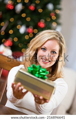 Christmas: Smiling Woman Holds Out Wrapped Christmas Gift - stock photo