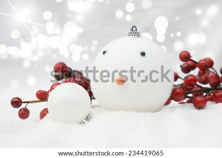 Christmas snowman bauble nestled in snow - stock photo