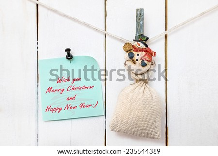 Christmas snowman clothespin hanging on clothesline or rope and holding sack and green Christmas greeting note paper with push black pin on wood background - stock photo