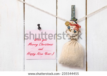 Christmas snowman clothespin hanging on clothesline or rope and holding sack and pink Christmas greeting note paper with push black pin on wood background - stock photo