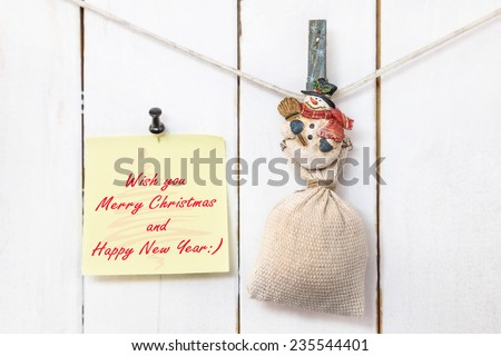 Christmas snowman clothespin hanging on clothesline or rope and holding sack and yellow Christmas greeting note paper with push black pin on wood background - stock photo