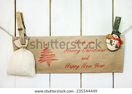Christmas snowman clothespins hanging on clothesline or rope and holding brown Christmas greeting card and sack on wood background - stock photo