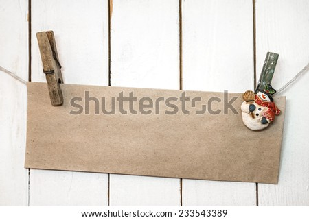 Christmas snowman clothespins hanging on clothesline or rope and holding greeting brown craft paper card on wooden background - stock photo