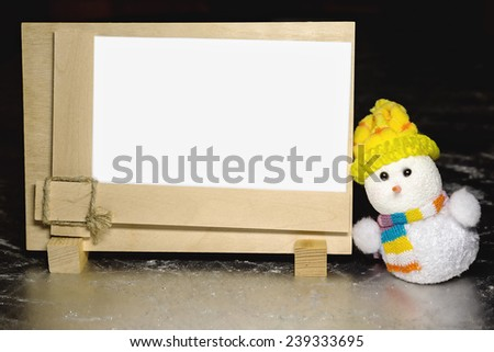 Christmas snowman toy and greeting blank wooden frame on silver or metal grunge surface - stock photo