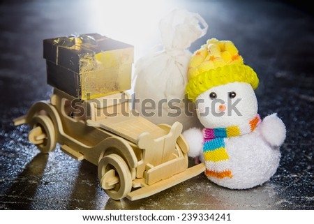 Christmas snowman toy and old vintage wooden automobile with golden or yellow gift box and sack on silver or metal grunge surface with backlight from behind - stock photo