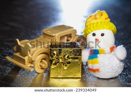 Christmas snowman toy and old vintage wooden automobile with golden or yellow gift box on silver or metal grunge surface with backlight from behind - stock photo