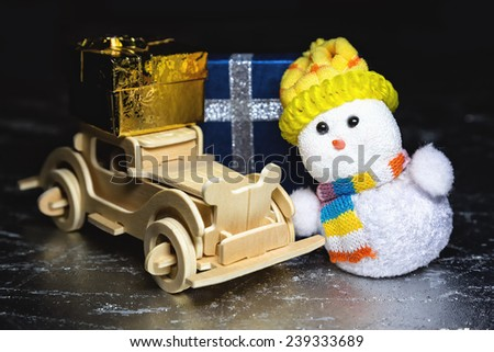 Christmas snowman toy and old vintage wooden automobile with golden or yellow gift boxes on silver or metal grunge surface - stock photo