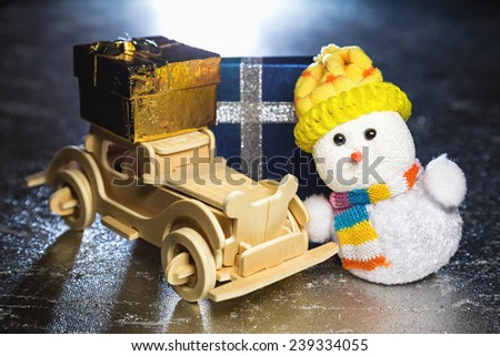 Christmas snowman toy and old vintage wooden automobile with golden or yellow gift boxes on silver or metal grunge surface with backlight from behind - stock photo