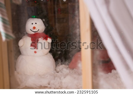 Christmas snowman viewed through a frosted window with open curtain standing in the winter snow outside in the darkness - stock photo