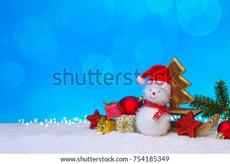 Christmas snowman with red scarf and santa claus hat , isolated on blue winter background.