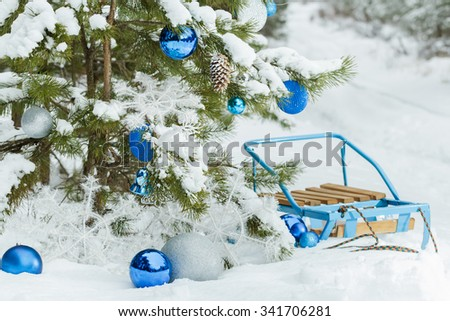 Christmas snowy pine tree decorated with glitter baubles and blue classic sledge on snow covering  - stock photo
