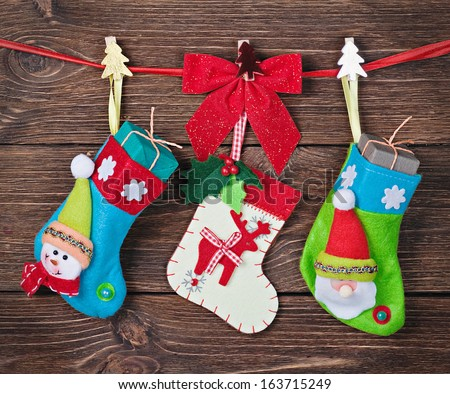 Christmas socks with gifts hanging on the wall - stock photo