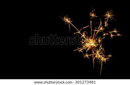 Christmas sparkler on black background. Bengal fire - stock photo