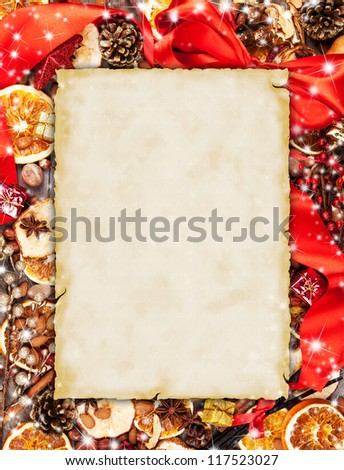 Christmas spices with dry orange and apple slices in frame with blank old paper