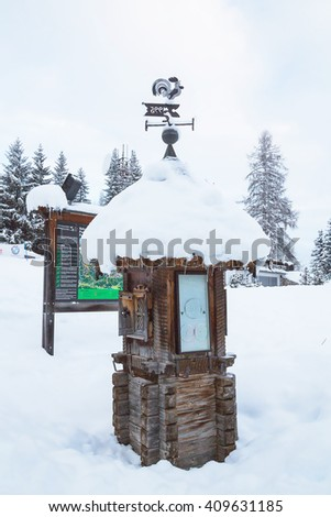 Christmas spirit in the mountain village with lots of snow. Information table with beautiful old wind-vane. - stock photo