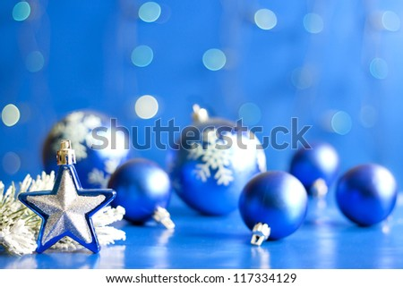 Christmas star closeup and baubles on blue blurred background - stock photo