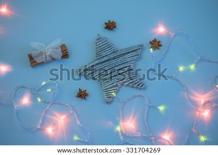 Christmas star in lights with cinnamon on cold background - stock photo