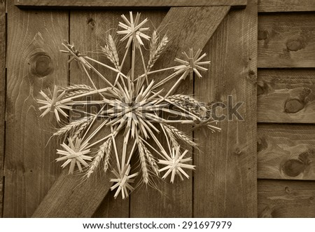 Christmas star (snowflake) made of straw on wooden wall of rural house in France. Aged photo. Sepia. - stock photo