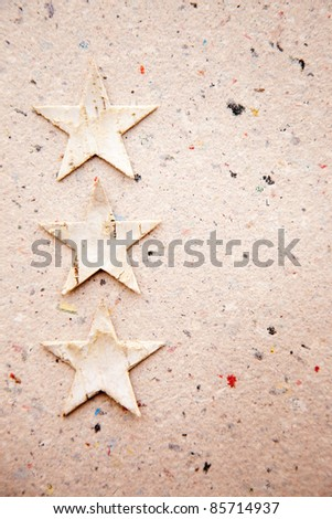 Christmas stars on recycled paper background as an ecology metaphor