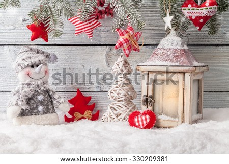 Christmas still life decoration with lantern, snowman and tree on wooden background