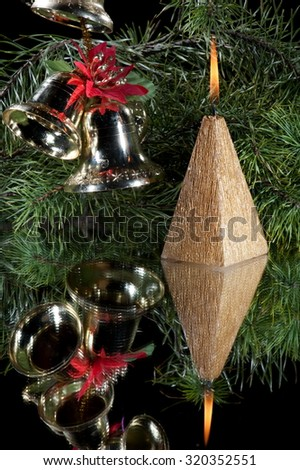 Christmas still-life from candles in the shape of a pyramid and the Christmas decorations, bells standing on the mirror, on the background of fir branches - stock photo