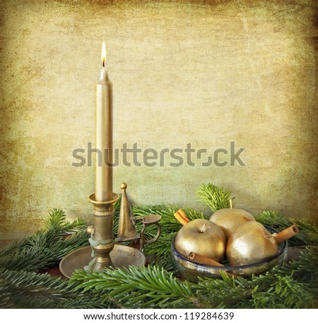 ChrIstmas still life: golden candle on a brass holder, 3 apples painted of gold in a bowl with cinnamon sticks on a bed of fir branches. - stock photo