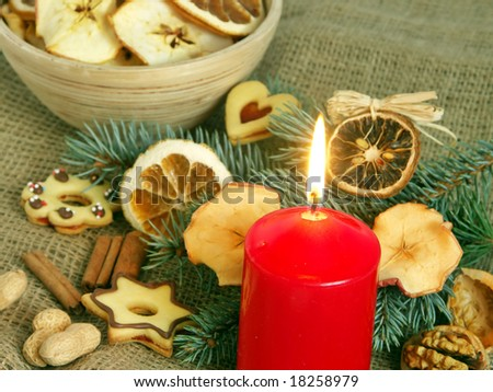 Christmas still life in red candle and dry fruit