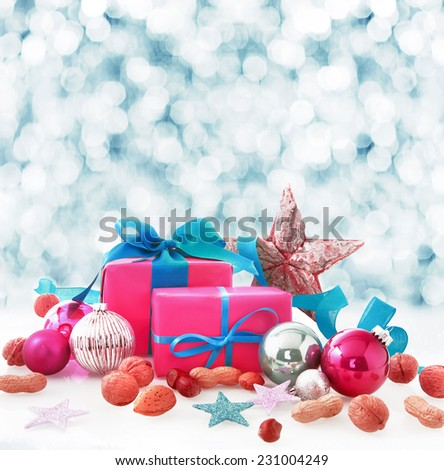 Christmas still life of colorful pink and blue gifts, stars, baubles and nuts in winter snow with a bokeh of falling white snowflakes behind and copyspace for your Xmas wishes - stock photo