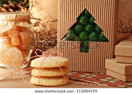 Christmas still life of food gifts with eco friendly wrapping paper and gift packaging (pine cones in background)  Close-up with shallow dof.  Selective focus on cookies tied with baker's twine. - stock photo